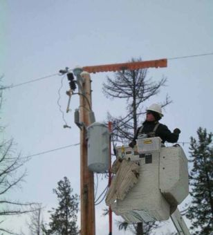 Lineworker in lift bucket works on pole